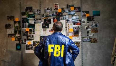FBI Agent in front of a picture board