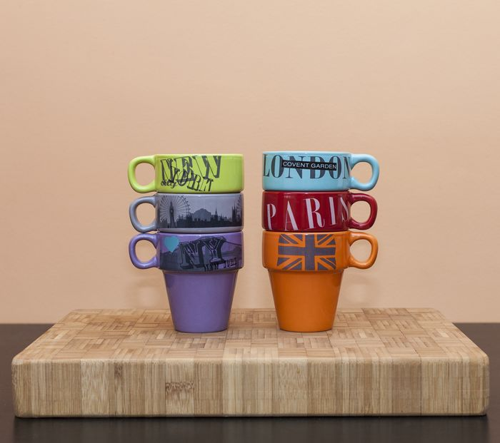 two stacks of colored coffee mugs with the names of different cities on them