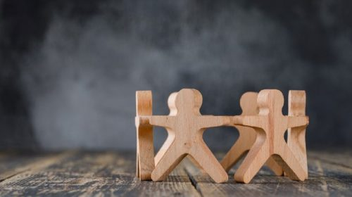 Wooden stick figures in a group